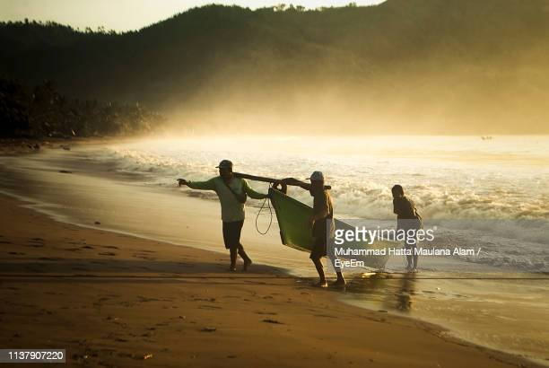 Fishermen Carrying Boat At Beach Against Sky During Sunset