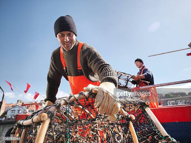 fishermen carrying lobster pots on boat - fishing boat stock pictures, royalty-free photos & images