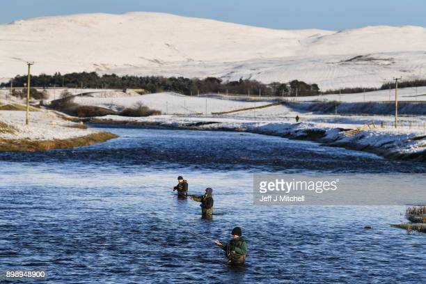 Fishermen cast their poles to catch fish in the River Clyde as temperatures drop across the country on December 27 2017 in Abignton Scotland...
