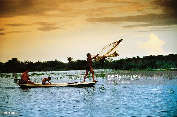 Fishermen casting a fishing net at sunset Amazon rainforest Brazil