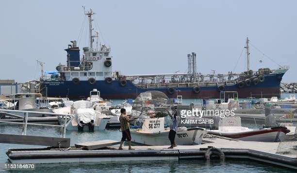 Fishermen check their net in front of ships docked in the port of Fujairah on July 2 2019 in the east of the United Arab Emirates where recent...