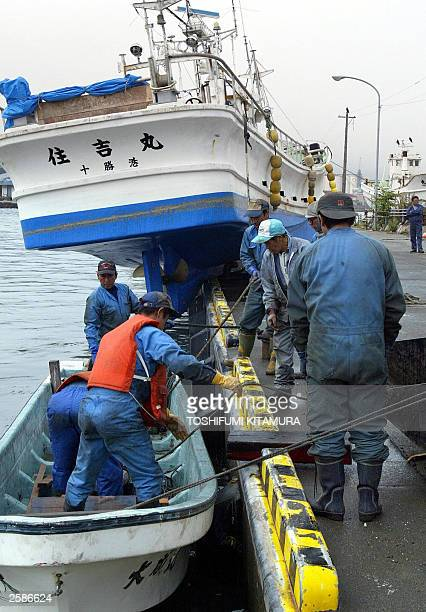 Fishermen clean up the dock beside the fishing boat SumiyoshiMaru which sits on the edge of the dockside after being washed out of the water from a...