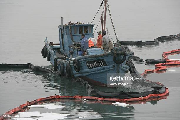Fishermen collect oil after a oil pipeline exploded on November 23 2013 in Qingdao China The death toll from the blast that occurred in Huangdao...