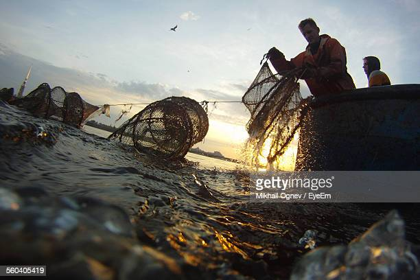 fishermen collecting net from sea against sky at sunset - fisherman stock pictures, royalty-free photos & images