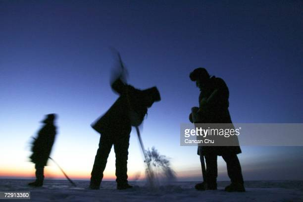 Fishermen drill a hole through the twofootthick ice to put their net into the frozen Chagan Lake before the sunrise December 30 2006 in Songyuan...
