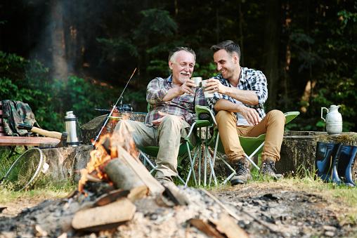 Fishermen drinking coffee beside bonfire 928803350