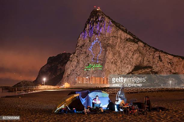 TOPSHOT Fishermen eat on the beach with Queen Elizabeth II projected on the Rock of Gibraltar in background to mark her 90th birthday on April 21...
