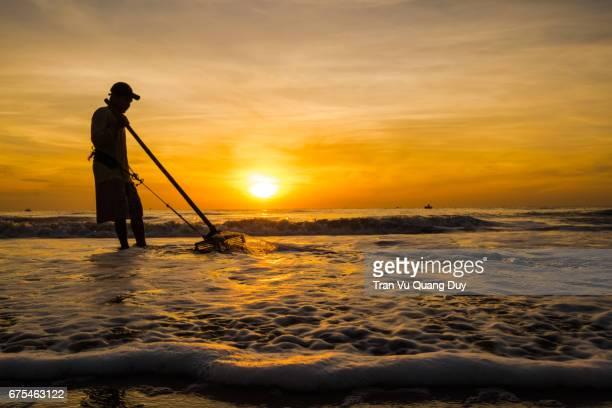 Fishermen fishing in the sea at dawn.