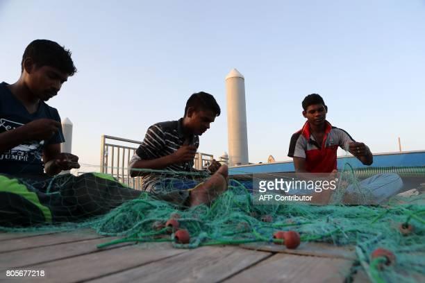 Fishermen fix a net on the corniche of the Qatari capital Doha on July 2 2017 / AFP PHOTO / STR