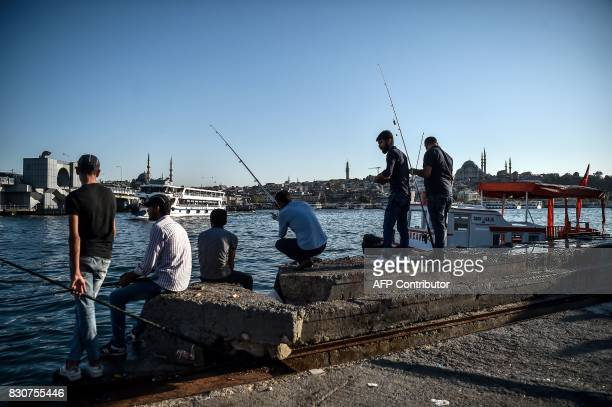 Fishermen gather on The Golden Horn in Karakoy District with Suleymaniye Mosque in the background in Istanbul on August 12 2017 / AFP PHOTO / OZAN...