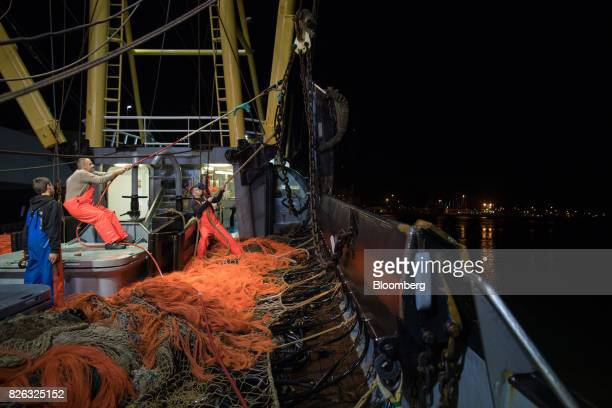 Fishermen haul in fishing nets as they prepare to unload their catch before sunrise at the port of Den Helder Netherlands on Friday Aug 4 2017 Prime...