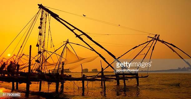 Fishermen hauling net at sunset in Kochi, India