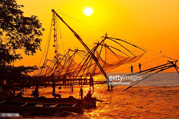 Fishermen hauling net at sunset in Kochi, India