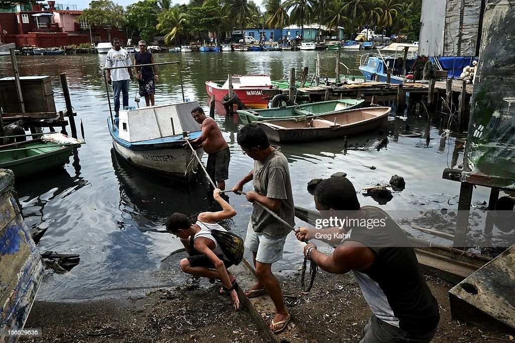 Fishermen help pull a stuck boat into a landing at a local dock November 16, 2012 in Havana, Cuba. Despite Cuba's fisheries being at critically low levels according to the United Nations, fishermen are still catching enough to make a living.