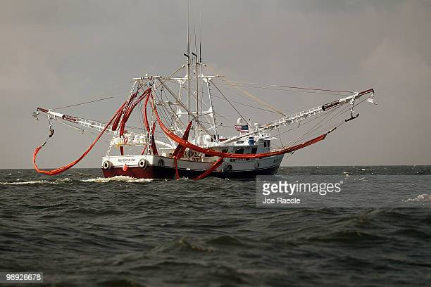 Fishermen helping with the effort to protect the coast line from the massive oil spill in the Gulf of Mexico are seen with oil booms hanging from...