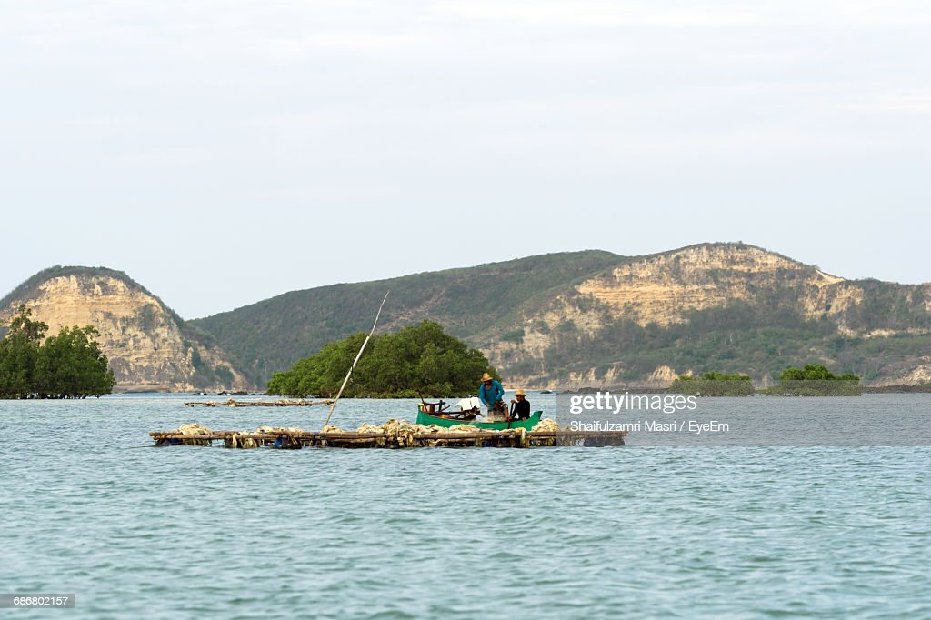 Fishermen In Fishing Boat On Sea Against Sky : Stock Photo