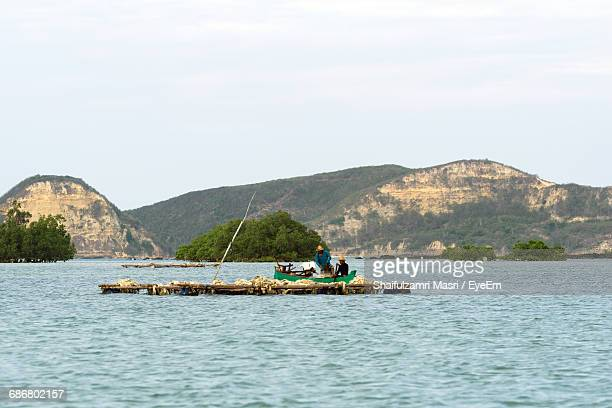 fishermen in fishing boat on sea against sky - shaifulzamri stock pictures, royalty-free photos & images