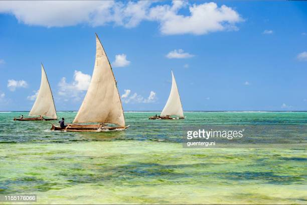 fishermen in their dhow boat at the coast of zanzibar - east africa stock pictures, royalty-free photos & images