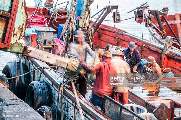 fishermen load ice onto their boat in hua hin, thailand - hua hin thailand stock pictures, royalty-free photos & images