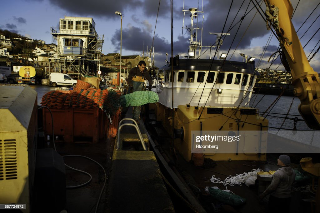 Fishermen load nets onto the St. Georges fishing trawler at sunrise in Newlyn harbor in Newlyn, U.K., on Tuesday, Nov. 28, 2017. Prime Minister Theresa May will pull Britain out of the 1964 London convention that allows European fishing vessels to access waters as close as six to twelve nautical miles from the U.K. coastline. Photographer: Annie Sakkab/Bloomberg via Getty Images