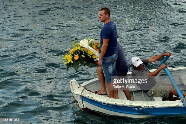 Fishermen look on before laying a wreath in memory of victims of a immigrants disaster over the Lampedusa shore on October 5 2013 in Lampedusa Italy...