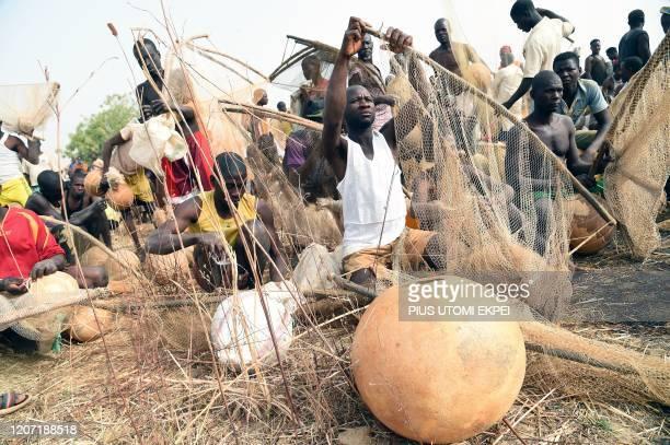 Fishermen mend fishing net to attend Argungu fishing and cultural festival at Argungu Town Kebbi State in northwest Nigeria on March 14 2020 Argungu...