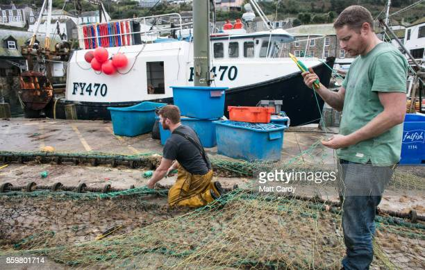 Fishermen mend their fishing nets besides the harbour in the village of Mevagissey which has submitted plans to limit the number of second homes on...