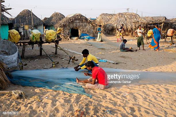 Fishermen mending fishing net in a village by the sea in Puri Puri a city in Odisha in India is situated on the Bay of Bengal It is famous for the...