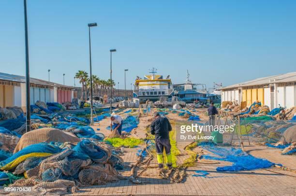 Fishermen mending nets in Villajoyosa Harbour