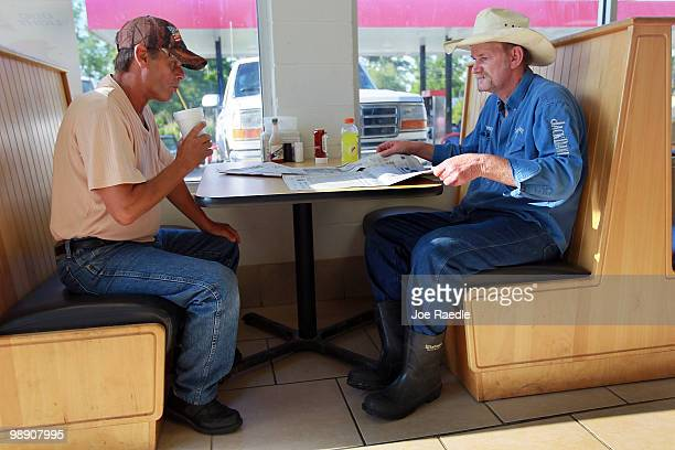 Fishermen Michael Calamari and Rudy Ladner pass the time at Kent Sue's Quick stop Deli store on May 7 2010 in Lakeshore Mississippi Fishermen are...