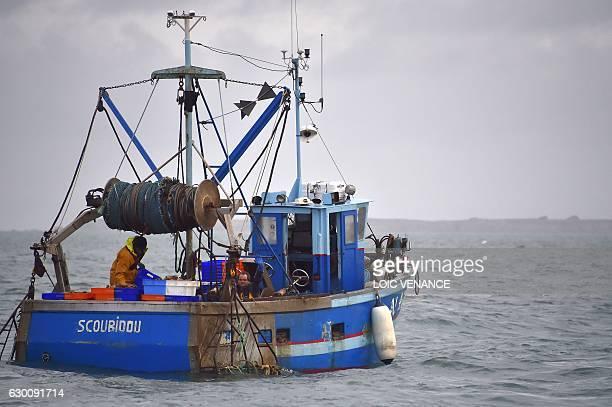 Fishermen on a boat fish scallops on December 15 2016 offshore BelleIleenMer western France / AFP / LOIC VENANCE