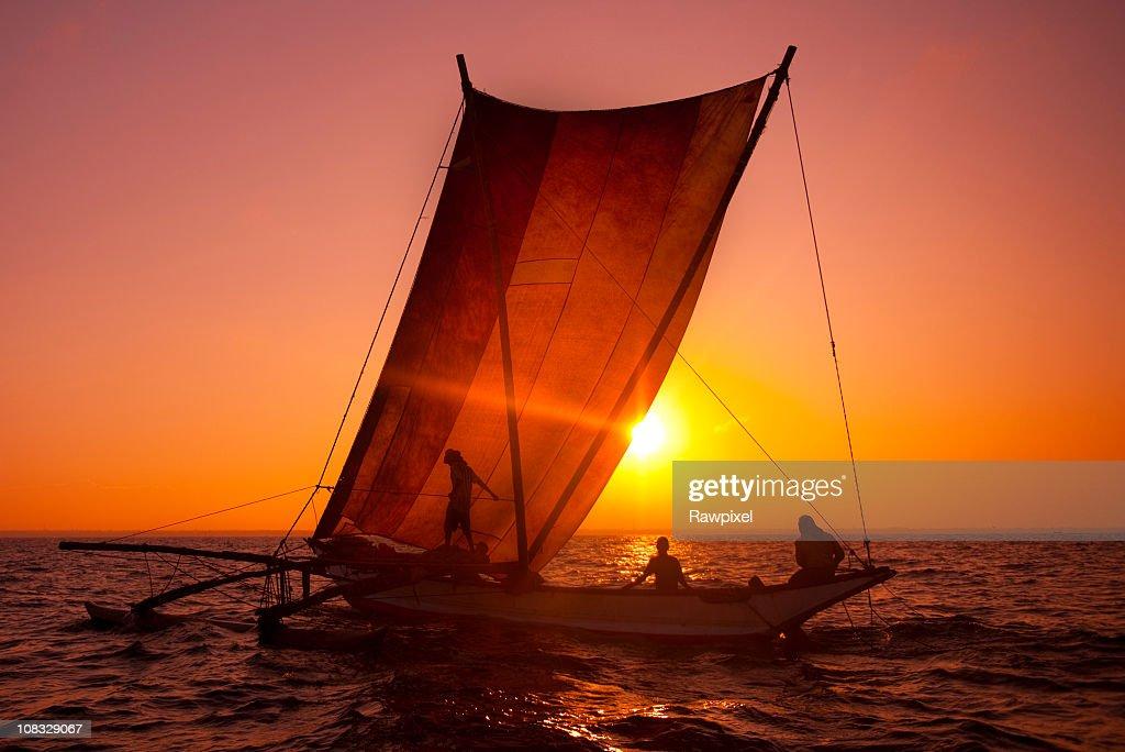 Fishermen on a catamaran at sunrise : Stock Photo
