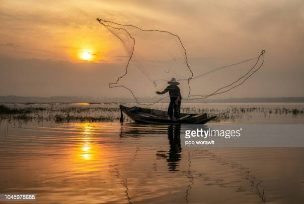 Fishermen on a rowing boat are fishing with a net.