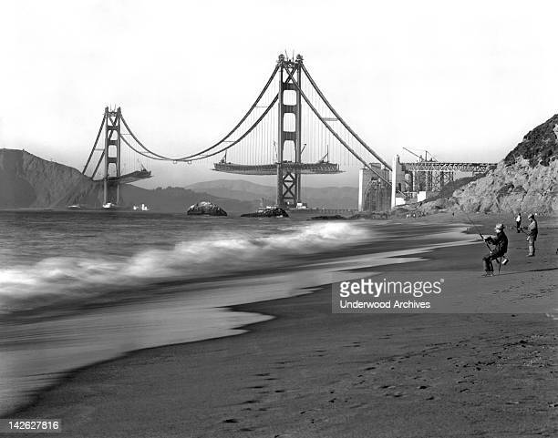 Fishermen on Baker Beach enjoy the view of the Golden Gate Bridge under construction San Francisco California 1930s