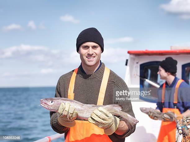Fishermen on boat holding fish