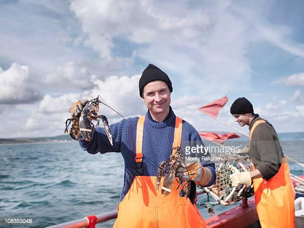 Fishermen on boat holding lobsters
