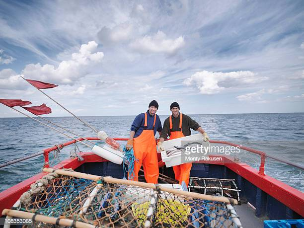 Fishermen on boat with fish