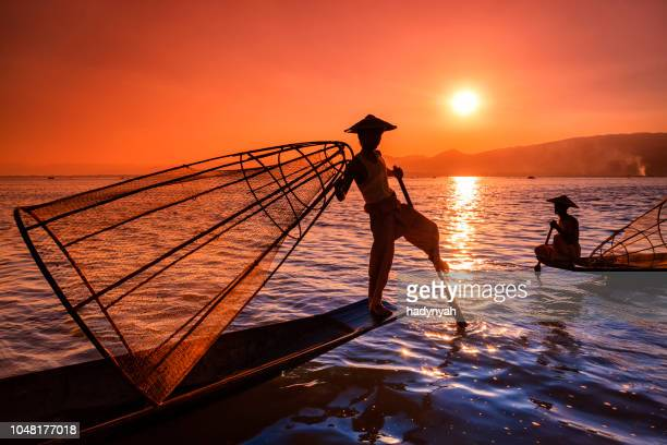 fishermen on inle lake watching the sunset, myanmar - inle lake stock pictures, royalty-free photos & images