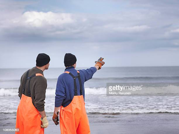 Fishermen on shore pointing out to sea