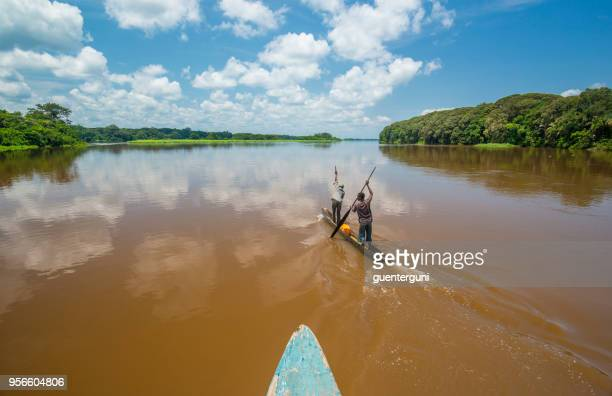 fishermen paddling in a typical dugout canoe (pirogue) on congo river - democratic republic of the congo stock pictures, royalty-free photos & images