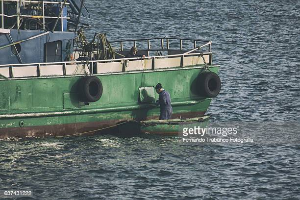 fishermen painting a fishing boat in a public seaport - カンタブリア ストックフォトと画像