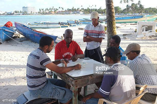 Fishermen play a game of dominoes while sitting at a table under palm trees on the beach near their boats on January 24 2014 in San Andres Colombia...