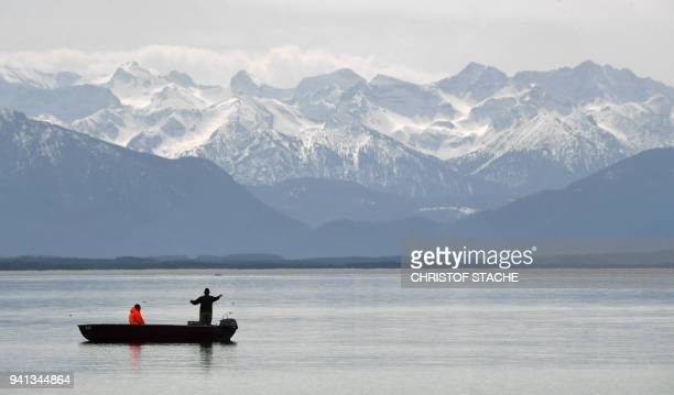 Fishermen prepare their fishernet in front of the Alp mountains at the lake Starnberger See near the village of Starnberg southern Germany during...