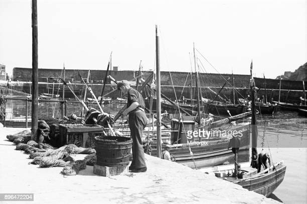Fishermen prepare their nets on the East Wharf Mevagissey July 1939