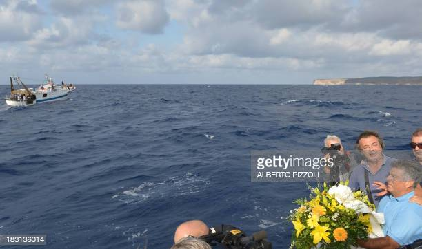 Fishermen prepare to put a bunch of flowers in the sea near the Lampedusa harbour on October 5 2013 after a boat with migrants sank killing more than...