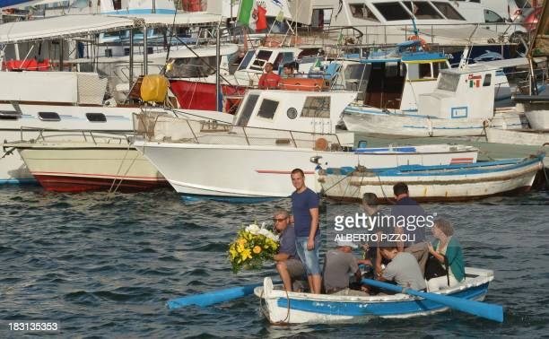 Fishermen prepare to put flowers in the Lampedusa harbour on October 5 2013 after a boat with migrants sank killing more than a hundred of people...