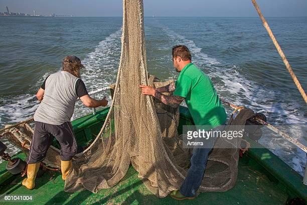Fishermen preparing fish net on board of shrimp boat fishing for shrimps on the North Sea