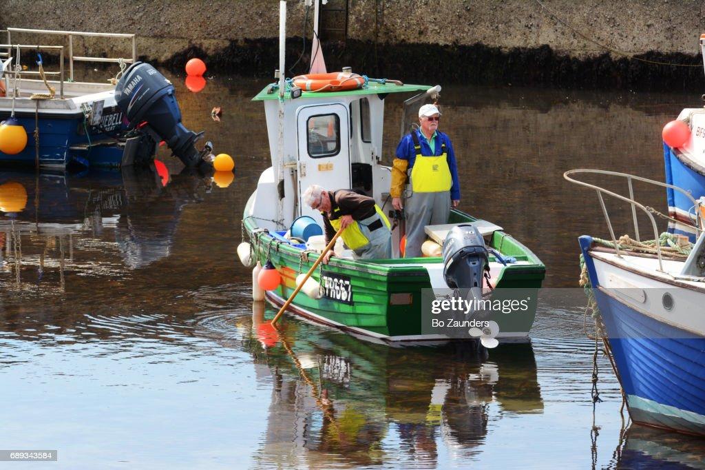 Fishermen preparing to go fishing, in Gardenstown, Scotland : Stock Photo