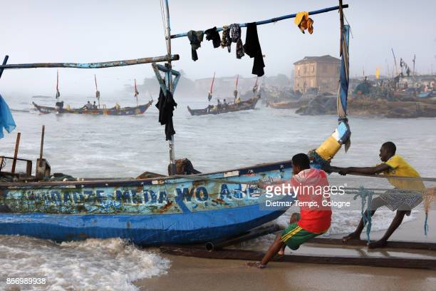 fishermen pull a boat in winneba, ghana - dietmar temps stock photos and pictures