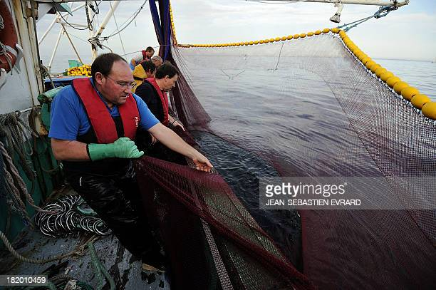 Fishermen pull out their nets from water aboard the fishing boat 'Kanedevenn' as they fish sardines on September 24 2013 in Quiberon western France...